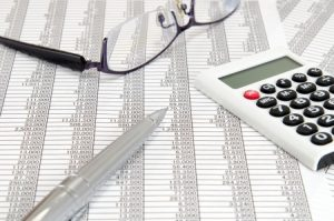 pen glasses and calculator for financial computation