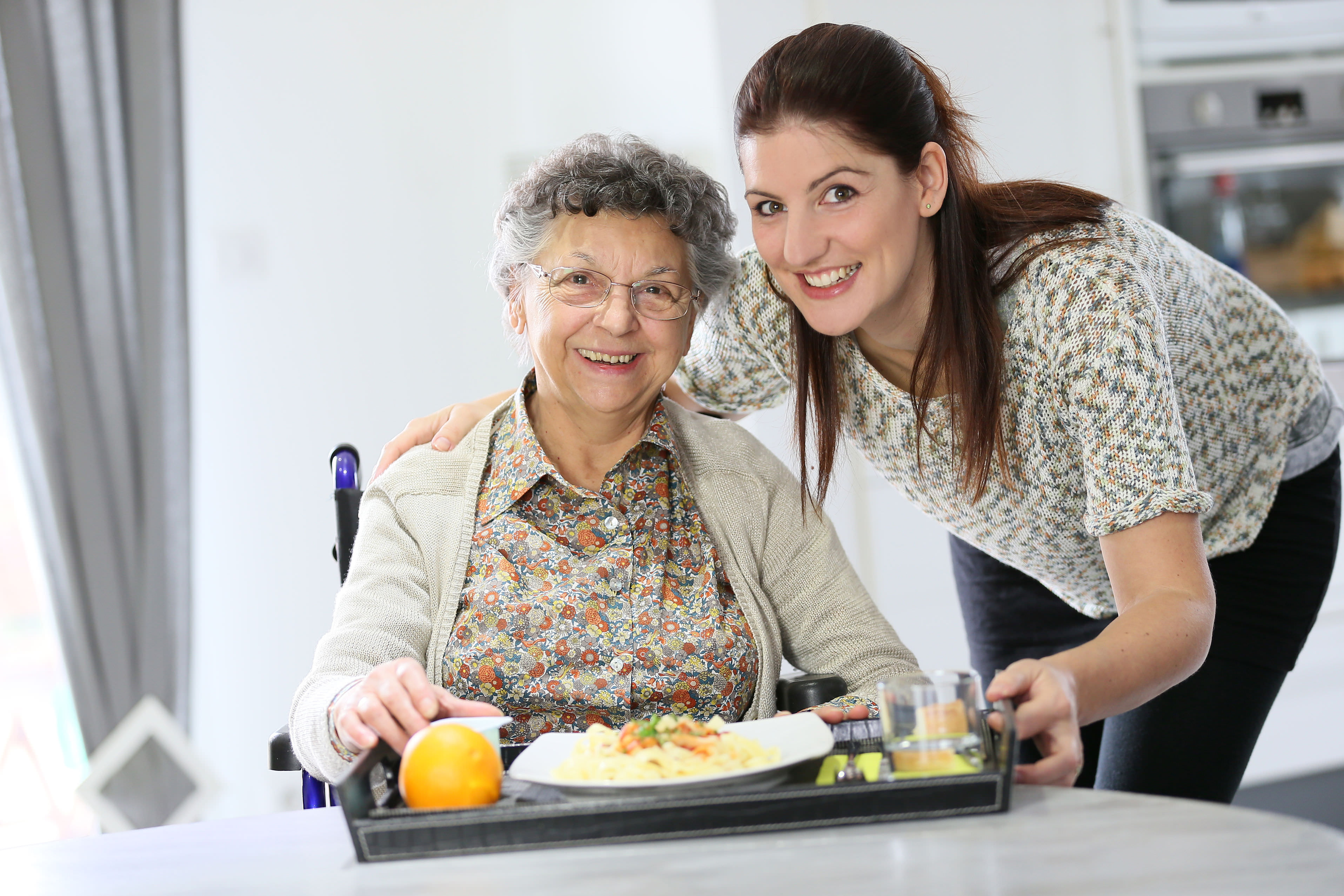 aged care worker serving a meal